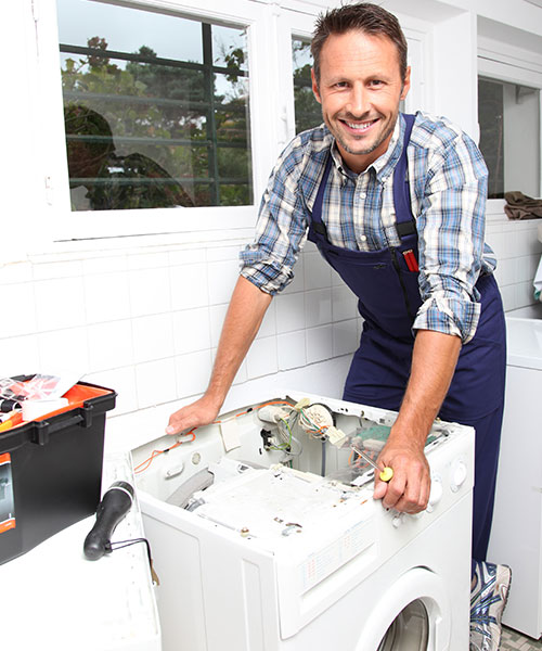 Smiling plumber standing over a disassembled washing machine