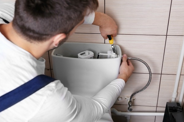 Plumber working on a running toilet