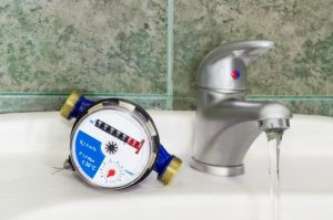 Not connected meter for consumption measuring of a cold water on a wash basin beside mounted handle mixer tap and water flowing from him on background of a wall with green tiles