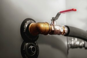 "Valve and bronze elbow in a boiler. Words ""sensor"" in french, german and italian languages. Phrases ""primary outlet"", ""warm water"" in french, german and italian languages. Close up."