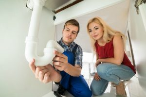 Male Plumber Showing Damage In Sink Pipe To Young Woman At Home